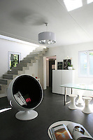 A bare concrete staircase connects the upper floor to the open-plan living/dining area which has a cool and uncluttered feel due to the simple contemporary furniture and understated grey-and-white colour scheme