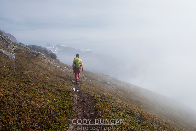 Female hiker hiking in cloudy weather while descending from summit of Volandstind mountain peak, Lofoten Islands, Norway