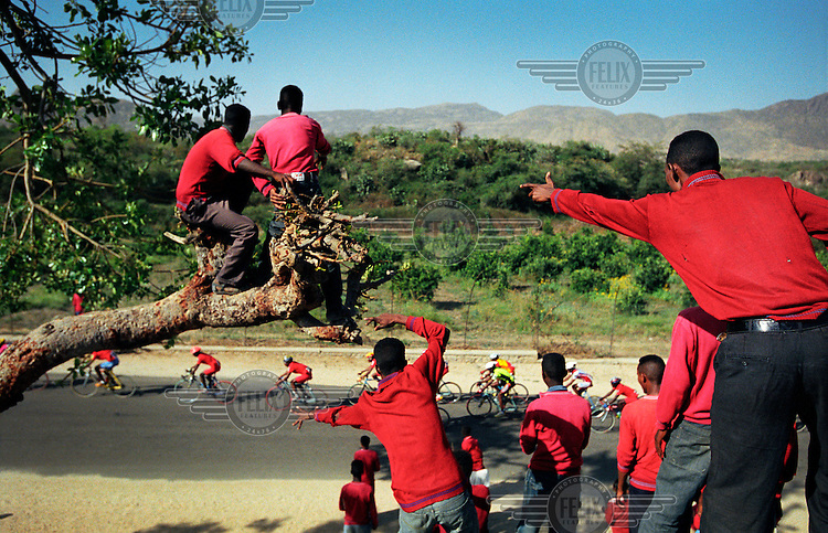 The Tour of Eritrea cycle race. Boys in their school uniforms cheer as the race passes by.