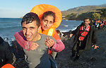 A refugee man carries a refugee woman as they walk along the coast after landing in an overcrowded rubber raft on a beach near Molyvos, on the Greek island of Lesbos, on October 30, 2015. They crossed the Aegean Sea from Turkey and were received by local and international volunteers. They then proceeded on their way toward western Europe. The boat was provided by Turkish traffickers to whom the refugees paid huge sums to arrive in Greece.