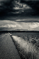 A black and white, split toned image of an old paved road fading into the distance with grass along the edge and a stormy sky above.