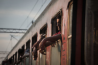 migranti al finestrino di un treno <br />