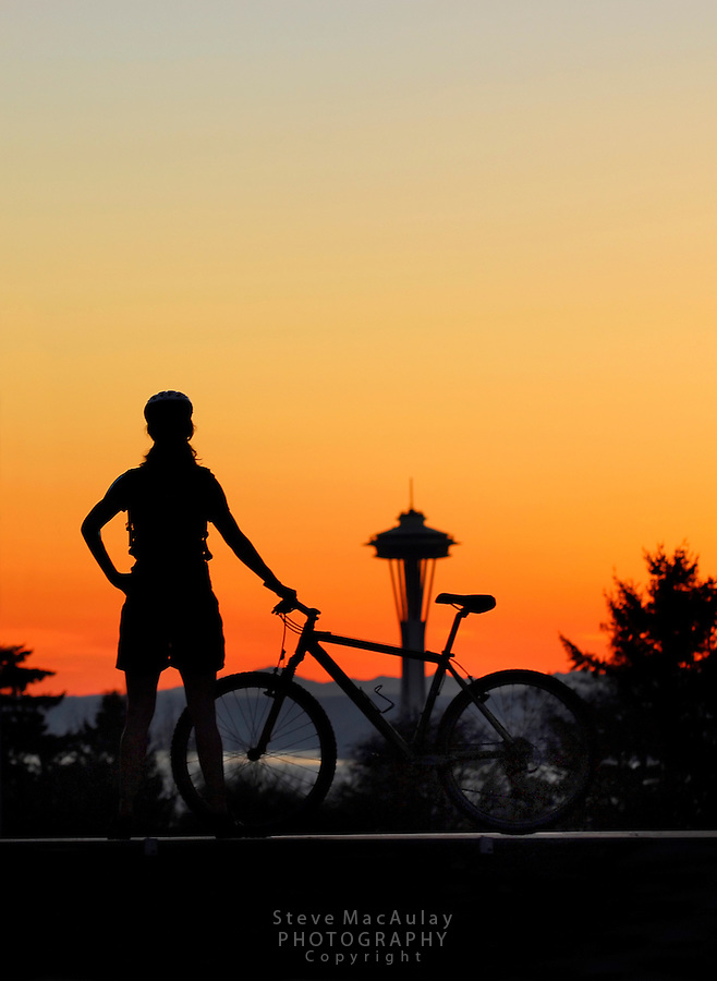 Female mountain biker checking out a colorful sunset and the Space Needle from Volunteer Park, Capitol Hill, Seattle, WA. ..Crop from horizontal - med. sharpening applied - no lightening