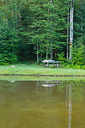 A man sleeping on pinic table next to Wildlife Pond at Bretzfelder Memorial Park in Bethlehem, New Hampshire