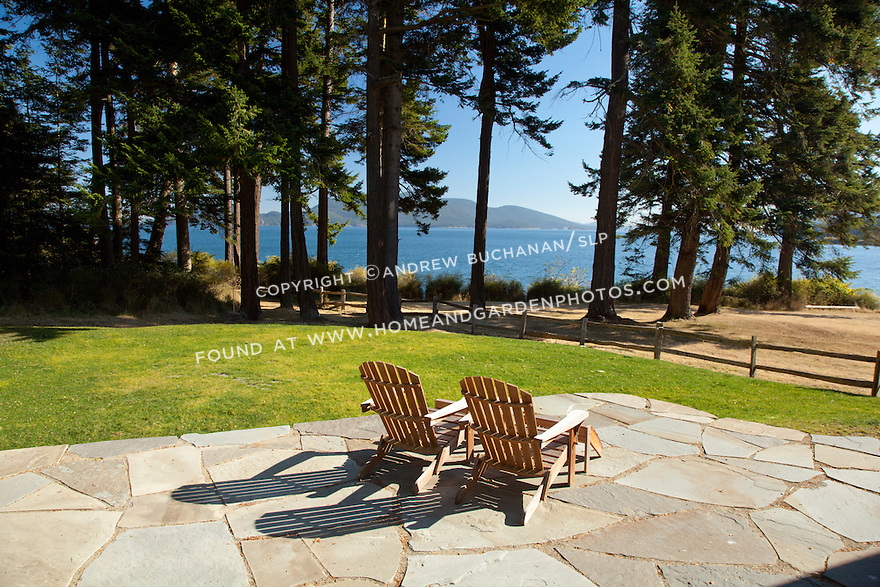 Two Adirondack chairs offer an inviting place to relax and look out over the water.