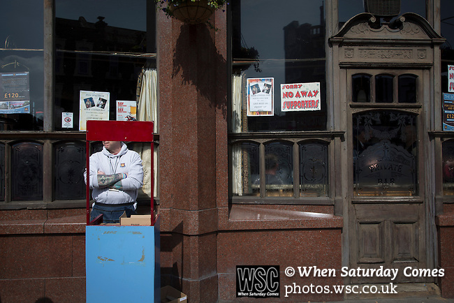 West Ham United 2 Crystal Palace 2, 02/04/2016. Boleyn Ground, Premier League. A programme seller on duty outside the Boleyn pub, a regular gathering place for home fans visiting the Boleyn Ground, pictured before West Ham United hosted Crystal Palace in a Barclays Premier League match. The Boleyn Ground at Upton Park was the club's home ground from 1904 until the end of the 2015-16 season when they moved into the Olympic Stadium, built for the 2012 London games, at nearby Stratford. The match ended in a 2-2 draw, watched by a near-capacity crowd of 34,857. Photo by Colin McPherson.