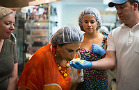 NWA Democrat-Gazette/CHARLIE KAIJO Preston Stewart, co-owner and chief chocolate officer, (right) holds cocoa butter for Theresa Northway of Bentonville (center) to smell, Sunday, May 13, 2018 at Markham &amp; Fitz Chocolate in Bentonville. <br />