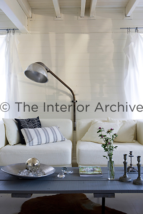 A pivoting antique wall light has been mounted between two armchairs in the living room