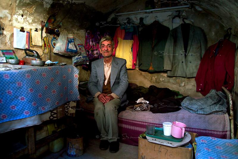 Baghdad, Iraq Feb 14, 2003.Mr. Abu Nagim, 76, a clothes repairer, lives alone in a 2m by 2m basement room in the Al Rashid souk.