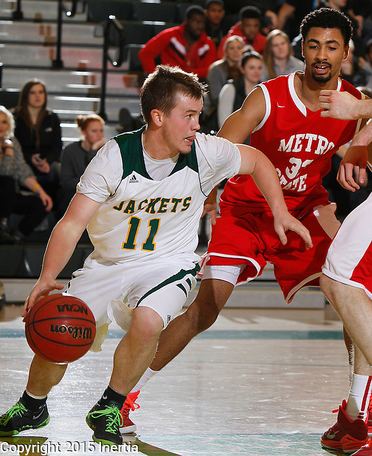 JANUARY 31, 2015 -- Wyatt Krogman #11 of Black Hills State dribbles away from Metro State defender Obi Kyei #33 during their Rocky Mountain Athletic Conference men's basketball game Saturday evening at the Donald E. Young Center in Spearfish, S.D.  (Photo by Dick Carlson/Inertia)