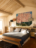 A painting of a cherry tree hangs on the wall behind the bed in this contemporary bedroom with an integrated rustic storage unit
