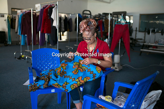 JULY 25: Bombix by Rose Bombo label makes alterations to her collection backstage before a show at Kinshasa Fashion Week on July 25, 2015, at the boxing gym at Shark club in Kinshasa, DRC. Local and invited foreign-based designers showed their collections during the 2015 edition of Kinshasa Fashion week. (Photo by Per-Anders Pettersson)