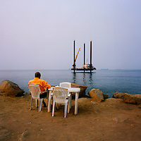A man sits on a chair looking out to sea toward an oil platform off the Ilha de Luanda..