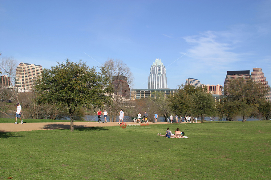 Sun bathers and joggers enjoy the perfect temperatures on the Hike and Bike Trail Town Lake Austin.