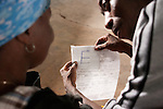 A patient has her sight tested by Abraham Adojo,  a Liberian clinic volunteer, at Buduburam Refugee Camp Community outreach center. The camp, a 1.5 hour drive from Accra, is for those displaced by the civil war in Liberia; the outreach center is a service of the Crystal Eye Clinic.