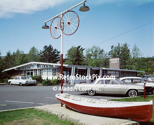 Bar Harbor Motel in Bar Harbor Maine. Restaurant Exterior with old cars and wooden boat.