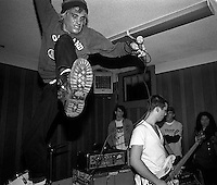 Operation Ivy's Jesse Michaels leaps from the drum kit during a performance at the Veterans Hall in Davis, California, 1987. Matt Freeman at right. photo copyright - Trent Nelson. http://www.trenthead.com