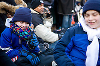 Aidan Woodruff shyly holds up a Barack Obama action figure while his brother Noah looks on at the inauguration of Barack Obama as the 44th President of the United States in Washington D.C. on January 20th, 2009.