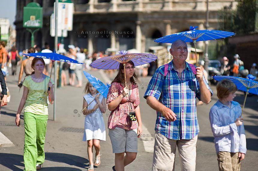 Tourists walk in downtown during a very hot day..Turisti a passeggio sotto il sole nel centro di Roma