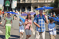 Tourists walk in downtown during a very hot day..Turisti a passeggio sotto il sole nel centro di Roma