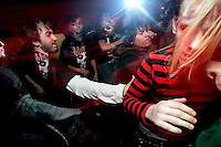 Punk fans dance in a mosh pit during a concert in the basement of the White House in Woodstock, Illinois.  The White House was a small suburban residential home rented by a group of 20-somethings in Woodstock, Illinois, a distant northwestern suburb of Chicago.  For about a year, the renters of the house staged punk-rock concerts in the house's small basement, without the approval of the neighborhood, local government, or police.  .