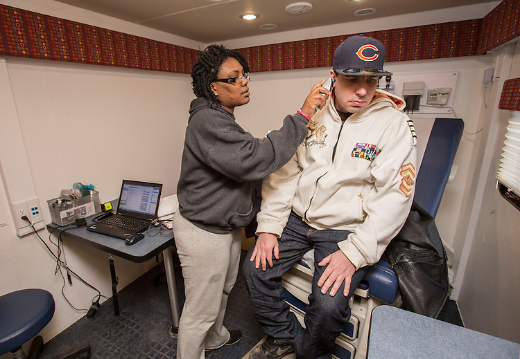 Linda Tanni, a nurse practitioner, sees the first of many patients as the Night Ministry's Health Outreach bus stops at Humboldt Park in Chicago Sunday, March 29, 2015. (DePaul University/Jamie Moncrief)