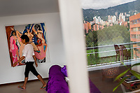 A Colombian webcam model, known as Flora Bella, walks through the dining room before performing a daily live show, broadcasted online from her apartment in Medellín, Colombia, 21 November 2016. With the traditional adoration of female beauty in Colombia, together with rapidly developing telecommunications technologies, the millennial generations of Colombian girls have turned the city of Medellín during the past few years into a one of the world centers of webcam modelling, a booming interractive sex industry. Thousands of young women stream everyday via websites that allow the global viewers to personally interract with a model and to pay them for sexually related acts. Although the core of the show is always based on stripping, the crucial part of a cam girl's success is communication. Cam models who have the ability of light conversation, flirting and entertaining the viewer earn thousands of dollars a month and have moved far beyond the borders of sexuality. Sharing their whole lives in a constant interaction with their online clients, they have built regular relationships in the cyberspace.