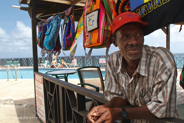 Barbadian man - vendor in red hat selling brightly coloured backpacks