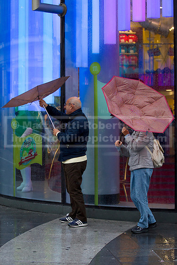 24/09/2012. LONDON, UK. Members of the struggle to keep their umbrellas under control as they attempt to stay dry in central London today (24/09/12). Rain and strong winds today hit the UK causing widespread disruption with gusts of up to 60mph predicted for the north of England and up to 80mm of rain predicted in some areas.. Photo credit: Matt Cetti-Roberts