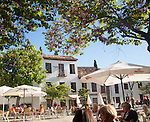 People sitting outside cafes historic square Placeta de San Miguel Bajo in the Albaicin district, Granada, Spain