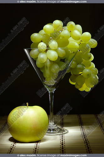 Grapes in a martini glass and an apple Artistic light-painted food still life