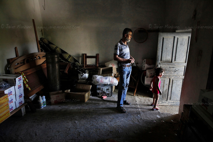 Anwar, a Free Syria Army supporter stands in his home in the Al Kassab region of northwestern Syria. His role in the conflict is to manage the food and medical supplies of his village. Most of the women and children have left this village leaving behind dozens of homes which bare the scars of constant shelling by the regime's tanks and artillery. His brother-in law was killed by a direct hit from a tank shell a few days prior - his body was never found. ..The Al Kassab region of northwestern Syria is considered the front line in the war against the Assad regime in this region of the country. This is the home to many sunni Muslims that are suffering the brunt of the shelling by the Assad army and air force - electricity was cut off months ago and basic food items along with petrol and potable water are increasingly in short supply. ..Still, the many groups that compose the Free Syria Army (FSA) in this region press on as the winter months approach. Most of the members of the FSA in this area are farmers, cell phone salesmen, clerks, carpenters, school teachers - most of them had little or no combat experience prior to joining the opposition army. Weapons and ammunition are also increasingly hard to come by as the price for bullets has skyrocketed since the conflict began 18 months ago. Rumors of an assault on this region by the Assad regime are part of everyday conversation in the villages that for the past few weeks have managed to keep the regime's army tanks and infantry out of their homes. ..© Javier Manzano