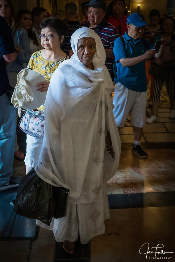 An Ethiopian Christian pilgrim visiting the Church of the Holy Sepulchre in the Christian Quarter of the Old City of Jerusalem.  The Old City of Jerusalem and its Walls is a UNESCO World Heritage Site.  This church was built over the site believed by many to be location of the death and burial of Jesus Christ.
