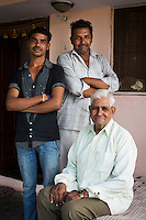 Three generations of cotton farmers: (L-R) Nitin Jat, 20, Chetan Jat, 42, and Bhagirata Jat, 72, pose for a family portrait in their home in Maheshwar, Khargone, Madhya Pradesh, India on 13 November 2014. Nitin, wants to continue doing Fairtrade cotton farming like the generations before him, but would like to also have a government job in the village so he can have an added source of income and pension (as did his grandfather). Photo by Suzanne Lee for Fairtrade