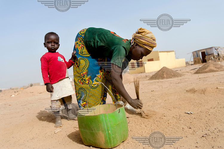 Talato Kabre, accompanied by her youngest child, Julien Rouamba (3), collects sand to sell for use in construction. It is her only income and she must sweep up sand, in a nearby open space, with a hand broom, sieving it, and then attempting to sell it. A small pile sells for CFA 1000 (GBP 1.30). She says she sometimes goes weeks without selling anything.