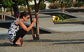 A woman takes a picture of the flowers she put on one of the benches of the Pentagon Memorial at the Pentagon in Washington, DC on September 11, 2013.  United States President Barack Obama will commemorate the 12th anniversary of the 9/11 terrorist attacks that killed nearly 3,000 people in New York, Washington and Shanksville, Pennsylvania.  There are 184 benches in the Pentagon Memorial representing the 184 people who died at the Pentagon on September 11, 2001.  <br /> Credit: Pat Benic / Pool via CNP