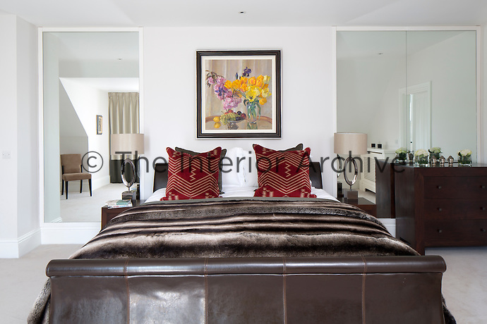 The master bedroom has a traditional feel with a leather sleigh bed and dark wood chest of drawers. Two full height mirrors reflect the room a give it a sense of space.