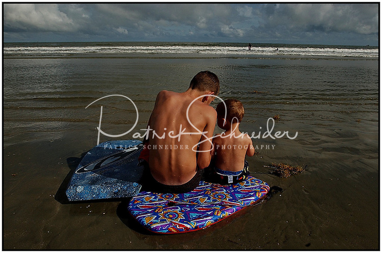 Two boys sit on boogie boards during a family vacation to the beach near Charleston, SC. There are three photos in this series of the boys with the suckers. Model released image may be used to illustrate other destinations or concepts.