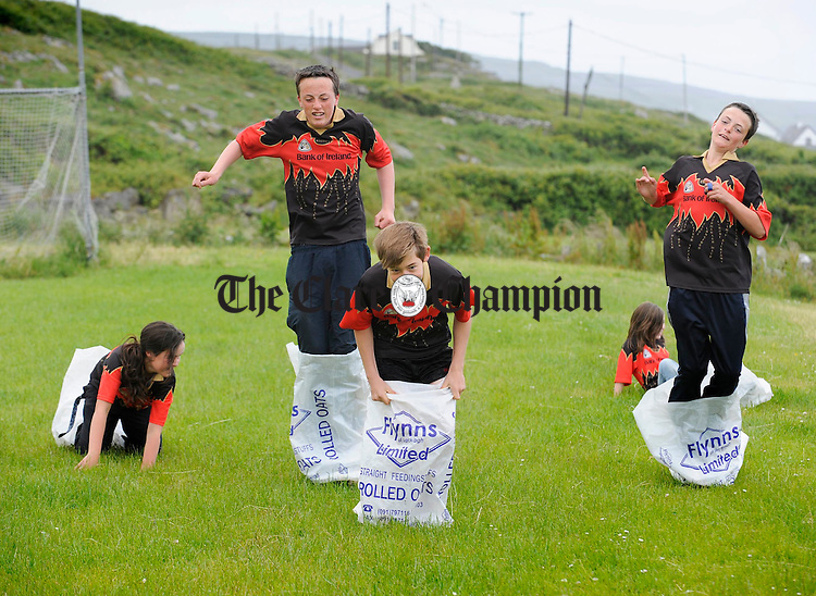 Martin Howard, Sean Kelly and James Howard lead the sack races from Aoife Howard and Lauren Prince during sports day at Fanore NS. Photogreph by John Kelly.