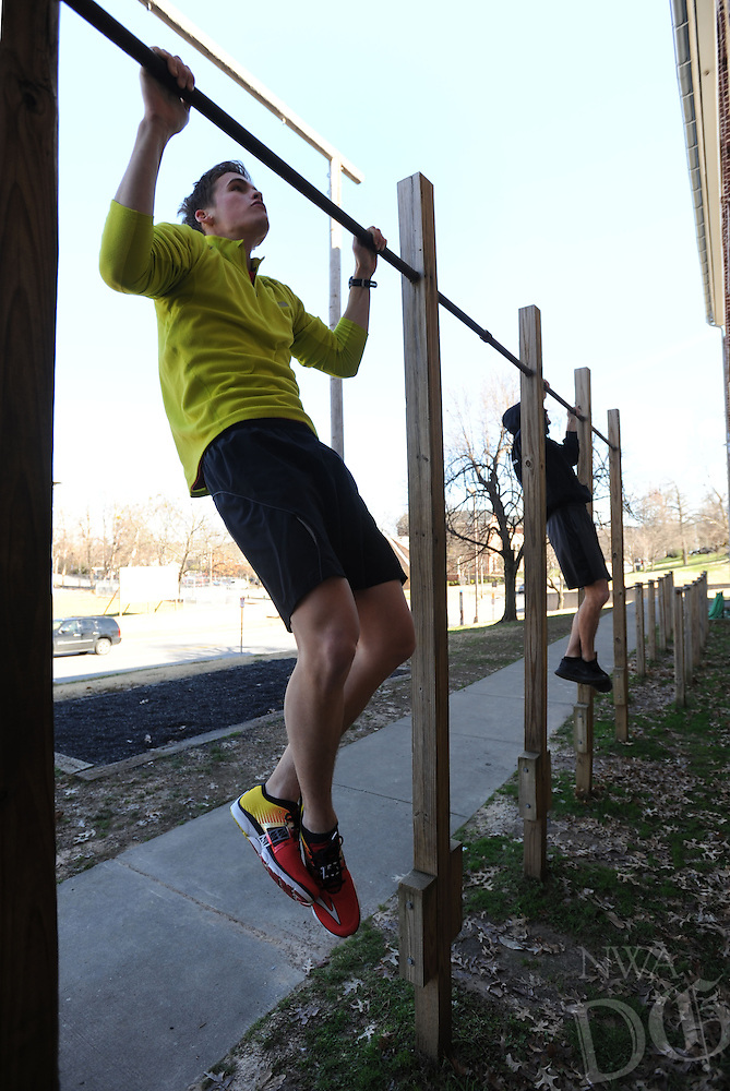 NWA Democrat-Gazette/ANDY SHUPE<br /> Eric Babcock (left) of Bentonville, a senior <br /> Army ROTC cadet at the University of Arkansas, and friend William Chavarria of Coos Bay, Ore., an active-duty Marine based in Camp Lejeune, N.C., do pull-ups Saturday, Jan. 2, 2016, while working out together at the ROTC facility on the university campus in Fayetteville. The two were taking advantage of the mild weather and exercising outside to maintain fitness.