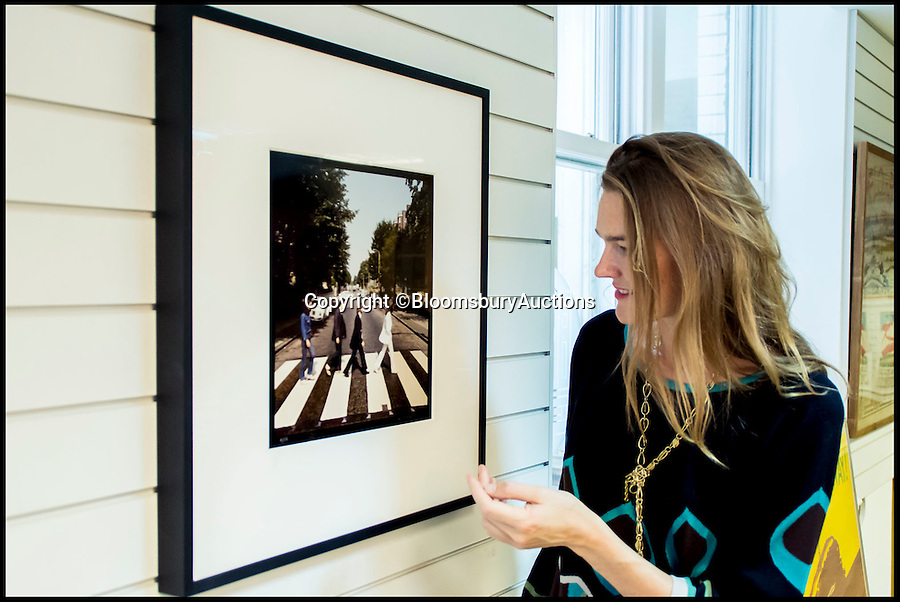 BNPS.co.uk (01202 558833)<br /> Pic: BloomsburyAuctions/BNPS<br /> <br /> ***Please Use Full Byline***<br /> <br /> Sarah Wheeler, Head of Photography at Bloomsbury Auctions with one of the framed out takes from the famous Abbey Road photoshoot. <br /> <br /> Rare photographs of the Beatles crossing Abbey Road shot for the cover of the last album they recorded together have emerged for sale for &pound;70,000.<br /> <br /> The six snaps were rejected as possible covers of the Beatles' famed Abbey Road album released in September 1969, just months before they split up.<br /> <br /> They were taken by Scots photographer Iain Macmillan, a close friend of John Lennon, who balanced precariously on a ladder in the middle of the road in north London for the shoot.<br /> <br /> He had just 10 minutes to get his shot so he got the Fab Four to walk back and forth continuously over the now famous zebra crossing.<br /> <br /> Also for sale is the photo that became the back cover of the album - a road sign with a blurred person in the foreground.<br /> <br /> Experts say the photos could make &pound;70,000 when they go under the hammer at Bloomsbury Auctions.