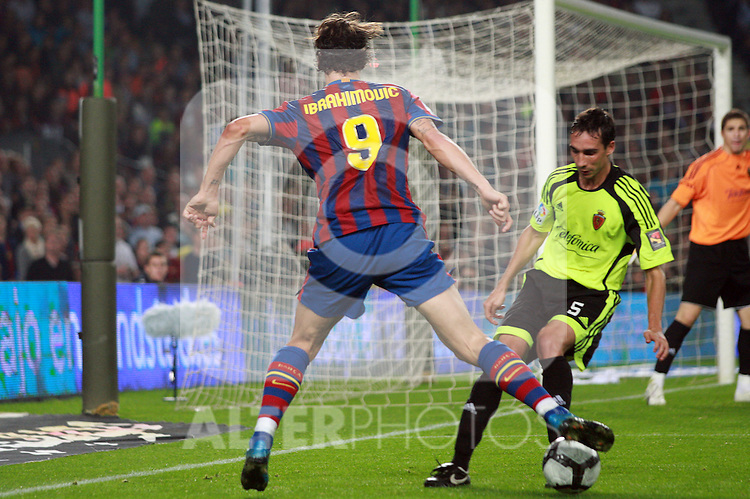 Football Season 2009-2010. Barcelona's player Zlatan Ibrahimovic (L) is challanged against Zaragoza's Pablo Amo (R) during their Spanish first division soccer match at Camp Nou stadium in Barcelona October 25, 2009