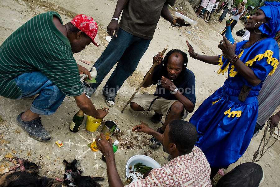 Haitians perform a ritual around a diagram made on the ground during the Voodoo ceremony in Saut d'Eau, Haiti, July 16, 2008. Every year in summer thousands of pilgrims from all over Haiti make the religious journey to the Saut d'Eau waterfall (100km north of Port-au-Prince). It is believed that 150 years ago the spirit of Virgin Mary (Our Lady of Mount Carmel) has appeared on a palm tree close to the waterfall. This place became a main pilgrimage site in Haiti since then. Haitians wearing only underwear perform a bathing and cleaning ritual under the 100-foot-high waterfall. Voodoo followers (many Haitians practise both voodoo and catholicism) hope that Erzulie Dantor, the Voodoo spirit of water, manifest itself and they get possessed for a short moment, touched by her presence.