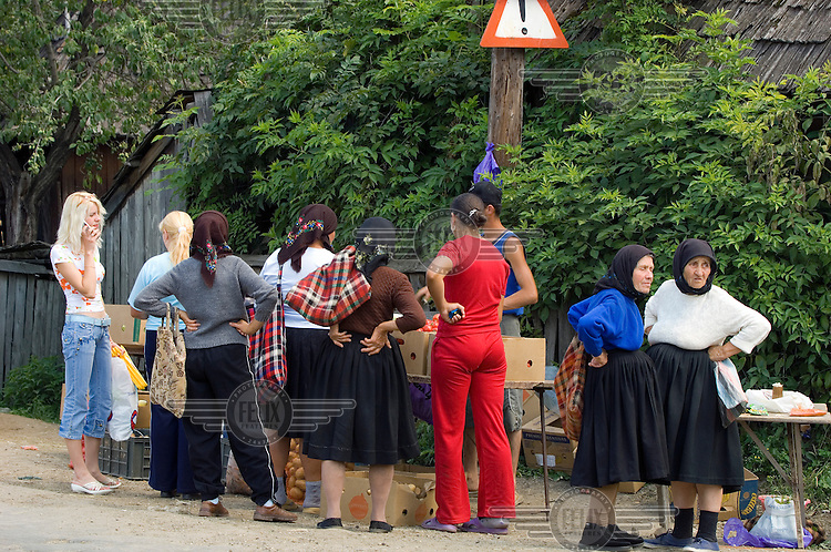 Women dressed in both traditional and contemporary clothes at market day in Sacel village.