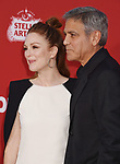 WESTWOOD, CA - OCTOBER 22: Actress Julianne Moore (L) and director/producer/screenwriter George Clooney arrive at the Premiere Of Paramount Pictures' 'Suburbicon' at Regency Village Theatre on October 22, 2017 in Westwood, California.