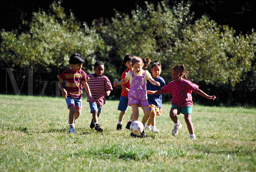 MULTI-ETHNIC GROUP OF YOUNG FRIENDS PLAYING SOCCER. SCHOOL CHILDREN. OAKLAND CALIFORNIA USA.