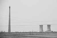 Daytime landscape view from a train of a commercial factory building site with cooling towers and a smokestack near Dàtóng Shì Chéng Qū in Shānxī Province, China  © LAN