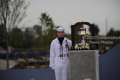 Arlington, VA - September 11, 2008 -- A United States Sailor rings the bell as the name of each person lost at the Pentagon is read during the Pentagon Memorial dedication ceremony Sept. 11, 2008. The national memorial consists of 184 inscribed memorial units honoring the 59 people aboard American Airlines Flight 77 and the 125 in the building who lost their lives Sept. 11, 2001..Credit: Jerry Morrison - DoD via CNP