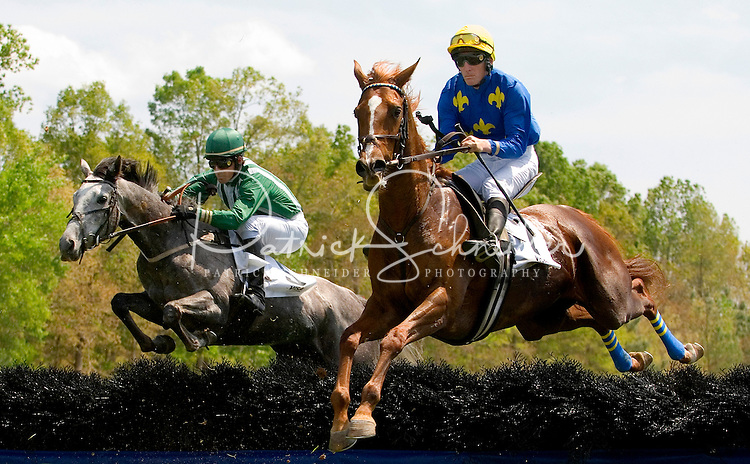 Two jockey's keep their focus as they jump over a hurdle during the Queen's Cup Steeplechase in Mineral Springs, NC.