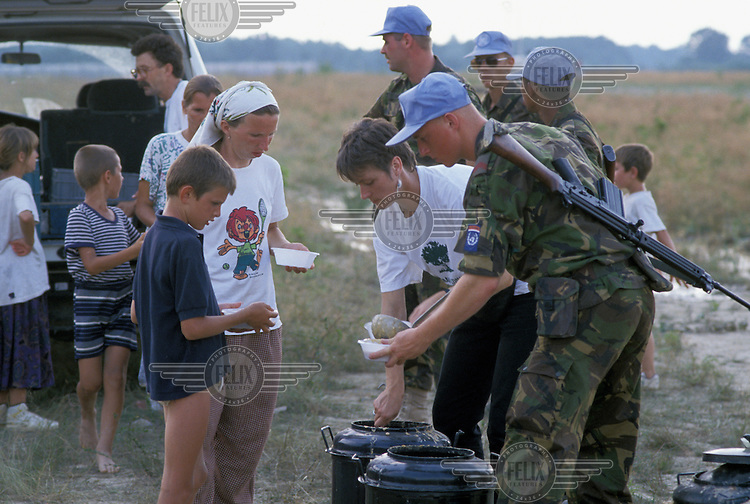 Dutch United Nations (UN) peacekeeping troops hand out food aid to Muslim refugees from Srebrenica at the airbase in Tuzla. The base was turned into a temporary camp to accommodate the thousands of internally displaced persons (IDPs) forced out of Srebrenica by the Bosnian Serbs in July 1995.
